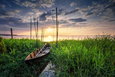 boatman: The wooden fisherman boat during the sunrise covered by thick green grass