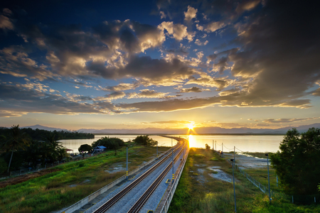 The ETS railway track cross the Bukit Merak lake. Taken during golden sunrise and beautiful clouds and blue sky