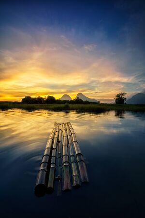 The fisherman bamboo raft under golden aurora sunrise at the Tasoh lake, Perlis, Malaysia Stock Photo