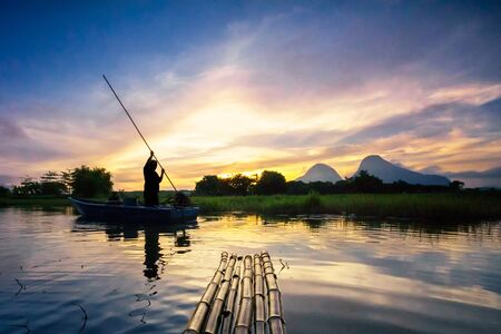 The fisherman in silhouette paddling the boat and the bamboo raft under golden aurora sunrise at the Tasoh lake, Perlis, Malaysia Stock Photo