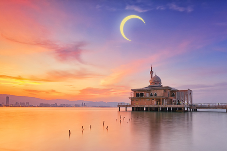 Floating Penang Port mosque during crescent moon and golden sunset Stock Photo
