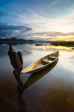 The boat docked on the lake side during beautiful golden sunset at Kwong lake, Rantau Panjang, Kelantan