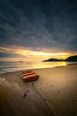 The boat under the dramatic cloud with golden sunset at Permatang Damar Laut, Penang beach. Stok Fotoğraf
