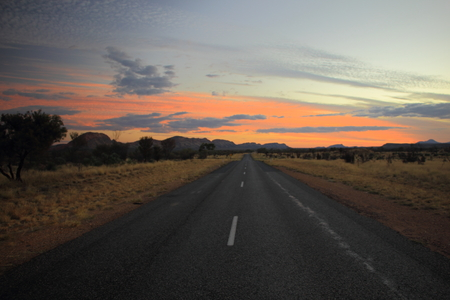 The Natmatjira Drive road and silhouette of West MacDonnell Ranges during sunset in the Australian Outback. The road is part of Red Centre Way in Northern Territory, Australia Banco de Imagens