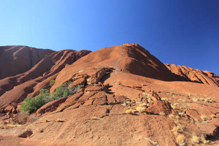 The base of the Ayers Rock or Uluru with people climbing up to its top.