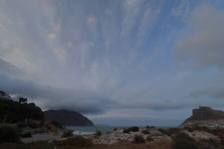 The view of Hout Bay Beach with sand dune and the sea with The Sentinel or Hangberg at right, and Constantiaberg mountain at left, looming in the background. Archivio Fotografico