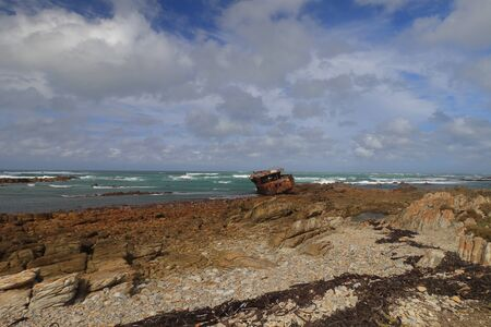 The rocky headland of Cape Agulhas which is the Southernmost Point of Africa with the wreck of Meisho Maru that run aground at this coast.
