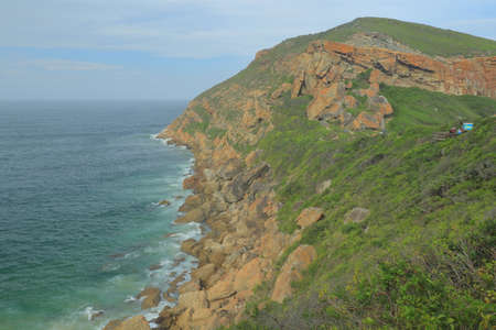 Rocky cliff shearing above the sea at Robberg Nature Reserve which is listed as  about 8 kilometres from Plettenberg Bay on Garden Route, South Africa.
