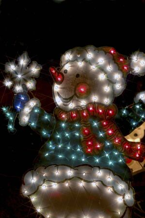 Snowman lawn decoration light up at night. photo