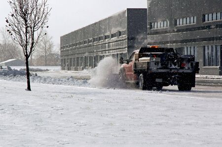 fresh snow: Snow plow cleaning up the parking lot. Stock Photo
