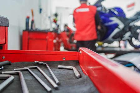 Motorcycle mechanics workshop, professional tools, selective focus.