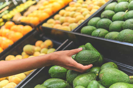 Young Woman Choosing Avocados in Grocery Store. Concept of healthy food, bio, vegetarian, diet. Selective focus.