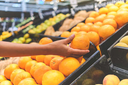 Young Woman Choosing Oranges in Grocery Store. Concept of healthy food, bio, vegetarian, diet. Selective focus.