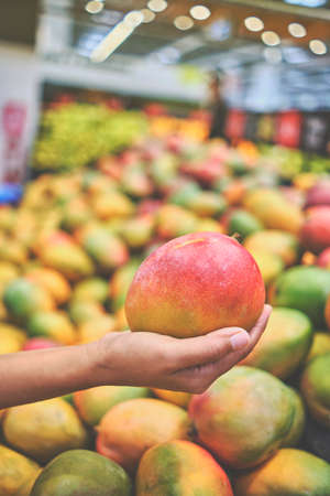 Young Woman Choosing Mango in Grocery Store. Concept of healthy food, bio, vegetarian, diet.