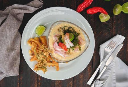 "Peruvian food: called ""Leche de tigre"" and ""chicharron"", Peruvian fresh fish on glass (Raw fish cocktail ceviche with lime, grinder, chili and cilantro). Selective focus Standard-Bild"