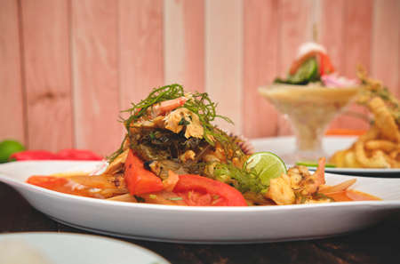"""Peruvian food: called """"Leche de tigre"""" and """"sudado de seafood"""", seafood (fish sweat, scallops, shrimp, octopus, snail, mixed with vegetables and spicy juice) top view. Selective focus"""