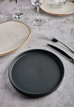 Empty plates, forks and glass of wine on gray concrete background. Top view. Concept mockup Imagens