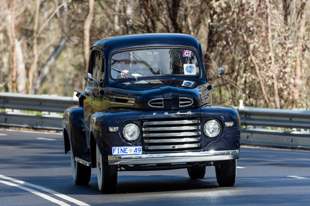 Adelaide, Australia - September 25, 2016: Vintage 1949 Ford F1 Utility (Ute) driving on country roads near the town of Birdwood, South Australia.