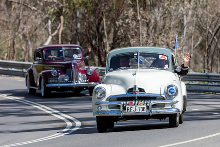 Adelaide, Australia - September 25, 2016: Vintage 1955 Holden FJ Sedan driving on country roads near the town of Birdwood, South Australia. Sajtókép