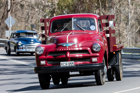 Adelaide, Australia - September 25, 2016: Vintage 1955 Chevrolet C1100 TrayTop Truck driving on country roads near the town of Birdwood, South Australia.
