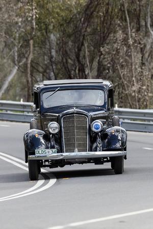 Adelaide, Australia - September 25, 2016: Vintage 1934 Oldsmobile Sedan driving on country roads near the town of Birdwood, South Australia.