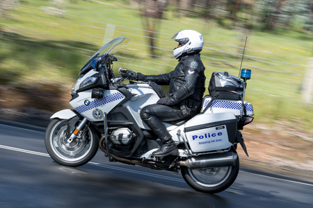 Adelaide, Australia - September 25, 2016: South Australian Police officer riding a BWM Police motorcycle on country roads near the town of Birdwood, South Australia.