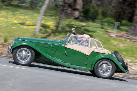 Adelaide, Australia - September 25, 2016: Vintage green 1954 MG TF Convertible driving on country roads near the town of Birdwood, South Australia.
