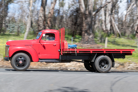 Adelaide, Australia - September 25, 2016: Vintage 1947 International KB8 Tray Truck driving on country roads near the town of Birdwood, South Australia.