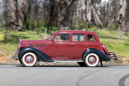 Adelaide, Australia - September 25, 2016: Vintage 1936 Plymouth Business Sedan driving on country roads near the town of Birdwood, South Australia.