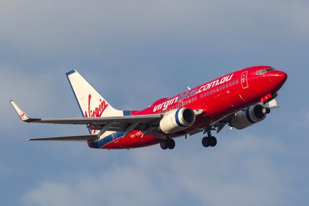 Melbourne, Australia - September 28, 2011: Virgin Blue Airlines Boeing 737-7Q8 VH-VBC turning on approach to  land at Melbourne International Airport. Banco de Imagens - 98564363