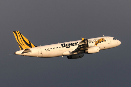 Melbourne, Australia - September 24, 2011: Low cost airline Tiger Airways Airbus A320-232 VH-VNK departing Melbourne International Airport with dark storm clouds behind. Editorial