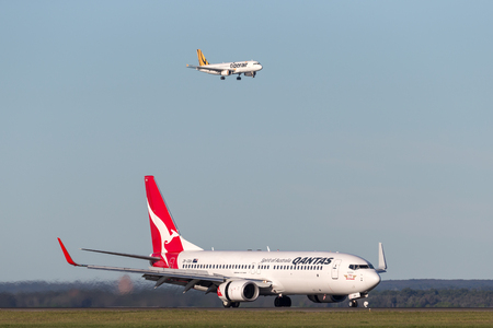 Sydney, Australia - May 5, 2014: Qantas Boeing 737-800 aircraft at Sydney Airport with a Tiger Airways Airbus A320 on approach in the background.