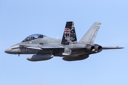 Albion Park, Australia - May 4, 2014: Royal Australian Air Force (RAAF) McDonnell Douglas FA-18B Hornet jet aircraft A21-110 flying against a blue sky.