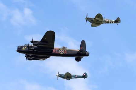 RAF Waddington, Lincolnshire, UK - July 5, 2014: Royal Air Force (RAF) Battle Of Britain Memorial Flight Avro Lancaster bomber PA474 flying in formation with two Supermarine Spitfire fighter aircraft. Editorial