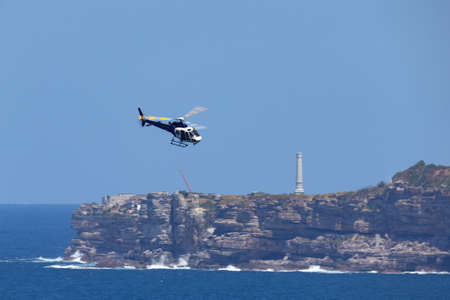 Sydney, Australia - October 11, 2013: Eurocopter AS 350B3 Helicopter VH-XGC conducting aerial filming over Sydney Harbour. Éditoriale
