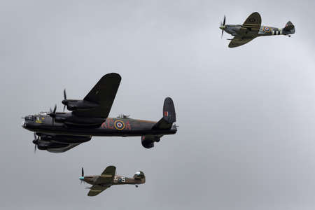 RAF Fairford, Gloucestershire, UK - July 13, 2014: Royal Air Force (RAF) Battle Of Britain Memorial Flight Avro Lancaster bomber PA474 flying in formation with a Supermarine Spitfire and a Hawker Hurricane.