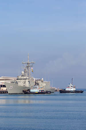 Melbourne, Australia - June 12, 2015: HMAS Melbourne (FFG 05) Adelaide-class guided-missile frigate of the Royal Australian Navy docking at Station Pier in Melbourne with the assistance of tug boats.