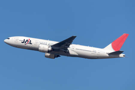 Sydney, Australia - October 7, 2013: Japan Airlines Boeing 777 large commercial aircraft climbing out on departure from Sydney Airport.