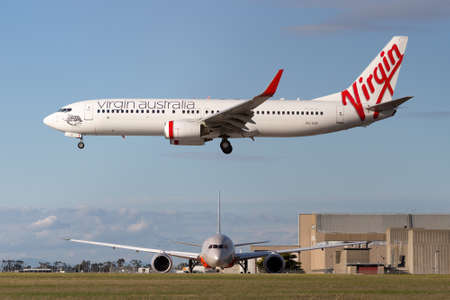 Melbourne, Australia - June 23, 2015: Virgin Australia Airlines Boeing 737-800 airliner about to land at Melbourne Airport while a Jetstar Airways Boeing 787 waits to depart. Editorial