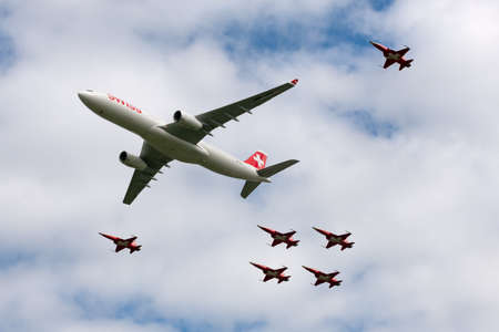 Payerne, Switzerland - August 30, 2014: Swiss International Air Lines Airbus A330 aircraft flying in formation with Northrop F-5 aircraft of Patrouille Suisse display team from the Swiss Air Force.