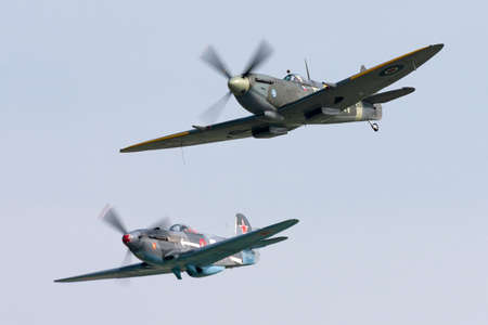 Payerne, Switzerland - September 5, 2014: Supermarine Spitfire Mk16e World War II fighter aircraft G-MXVI flying in formation with Yakovlev Yak-3M. Editorial