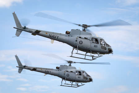 Avalon, Australia - February 26, 2015: Royal Australian Navy Aerospatiale AS-350B Helicopters (N22-001 & N22-016) from HMAS Albartoss flying in close formation.