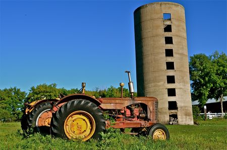 old tractors: Old tractors and an even older silo provide a glimpse of farming many years ago  Stock Photo