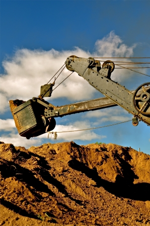 dragline: The old dragline is extend is ready to excavate soil from a huge dirt pile   Stock Photo