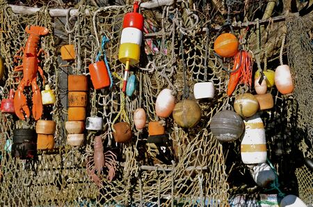 A brightly colored collection of buoys and lobster related items are displayed on a net  스톡 콘텐츠
