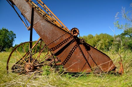 The old rusty hay walker is parked in long grass