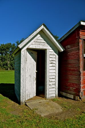 privy: An old white outhouse with a door half open stands next to a red shed  Stock Photo