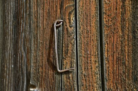Old rusty hook is mounted on an extremely weathered door