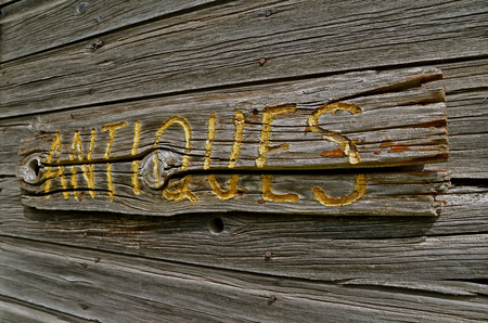 Carved ANTIQUES sign on old weathered wood Imagens - 27080689