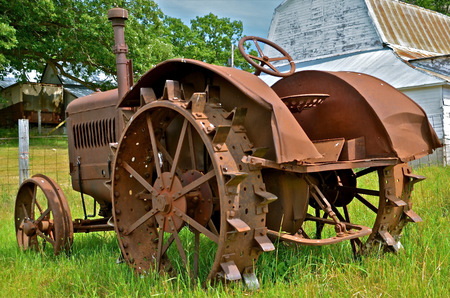 lugs: Antique tracter parked behind the barn